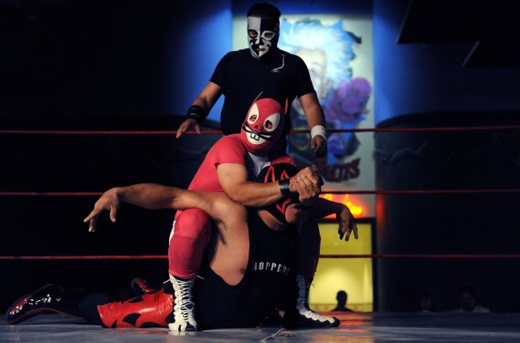 Super Conejo puts a wrestler in a hold at a match in Denver, Colo., on Sunday, May 24, 2009. For the past 3 years IWF Lucha Libre has held authentic Mexican style wrestling matches featuring local and Mexican wrestlers at different venues in Colorado. Matches occur about once per month. El Escorpio is in the background. (Chris Schneider/Chris Schneider Photography)